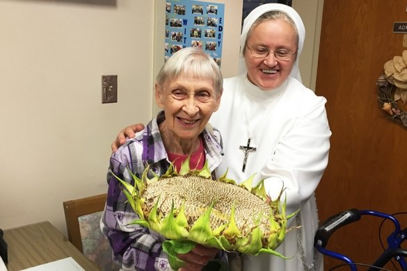 St. Joseph's sister with resident and sunflower